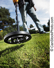 Metal Detector - Man finding a gold ring in grass using a...