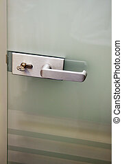 Metal door handle and the lock on a glass door