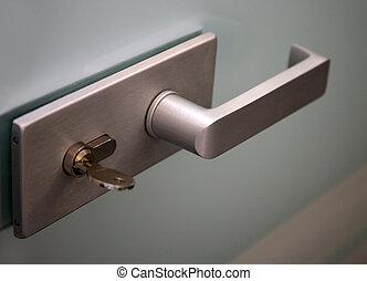 Metal door handle and the lock on a glass door