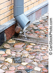 metal downspout on brick building with water flowing from it in heavy rain