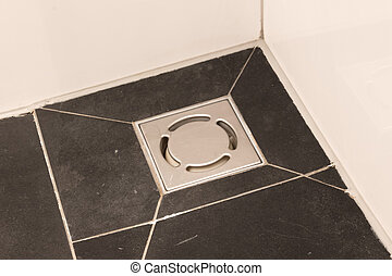 Metal drain hole in the tiled floor