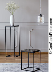 Metal end table standing on carpet in real photo of bright...