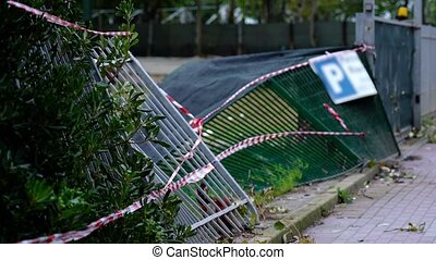 Metal fence lies on ground protected by white and red tapes...