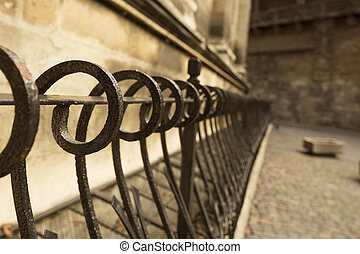 Metal fence near the stone wall l in Lviv