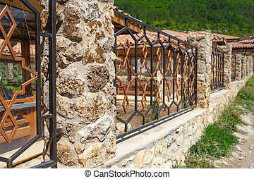 Metal fence with columns of stone and cement ..