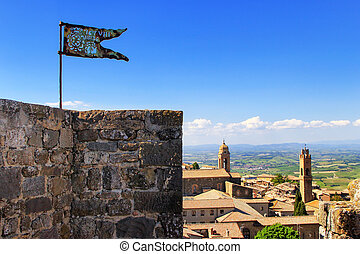 Metal flag on the top of Montalcino Fortress tower in Val d'Orcia, Tuscany, Italy