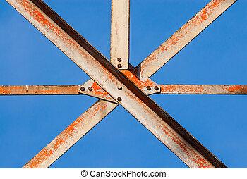 Metal girders crossing with screws. - Worn metal girders ...