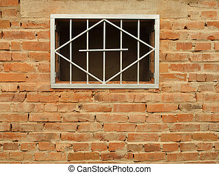 Metal grid in the window a brick wall