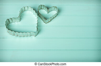 Metal heart shaped cookie cutters on a retro turquoise...