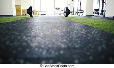 Metal heavy barbell laid on the floor in modern gym. - Close...
