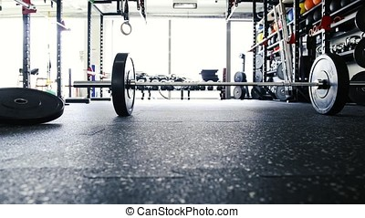 Metal heavy barbell laid on the floor in modern gym.