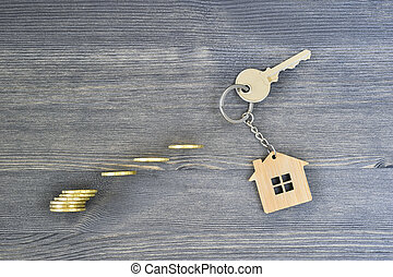 Metal key lock new home with wooden keychain on a wooden rustic gray background with shiny yellow coins.