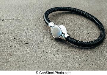 Metal key pendant on dark concrete background