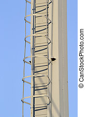 Metal ladder on blue sky background .