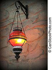 Metal lantern on a old stone wall
