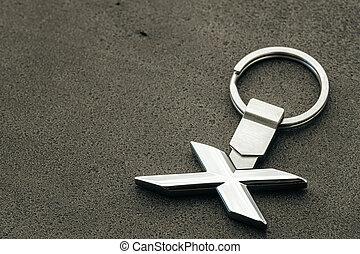 Metal letter X car key on dark concrete background
