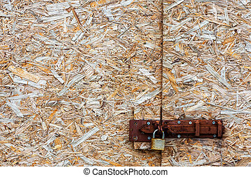 Metal lock on an abstract background compressed wood chippings b