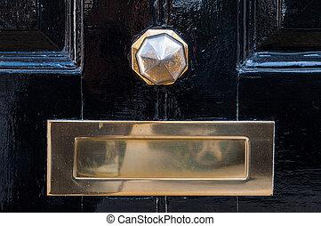 Metal mailbox and door knob on a black painted door