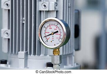 Metal manometer - Close up of metal manometer with machinery...
