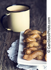 Metal mug full of coffee and a plate of koeksisters in artistic conversion