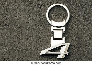 Metal number Four car key on dark concrete background
