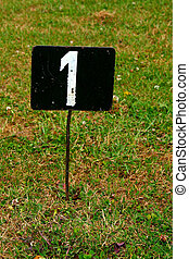 Black metal plate with white number in grass
