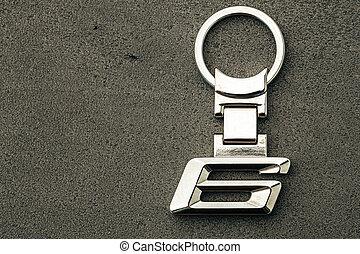 Metal number SIX car key on dark concrete background