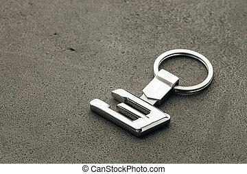Metal number Three car key on dark concrete background