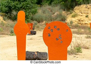 Metal orange popper targets on the range. Close-up