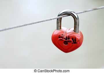 Metal padlock in the form of heart on fence
