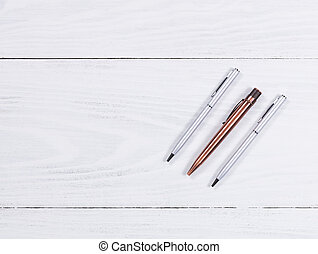 Metal pens on white wood background