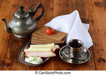 Metal plate with crispbread, cheese, cottage cheese, ham, cherry tomato, cup of coffee, coffee pot on a wooden background. Healthy breakfast. Healthy eating concept.