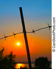Metal pole with barbed wire against the setting sun