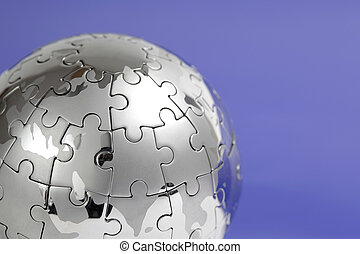Metal puzzle globe, close-up on blue background