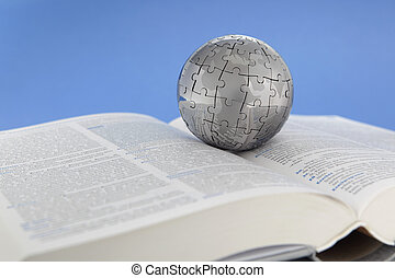 Metal puzzle globe on open book