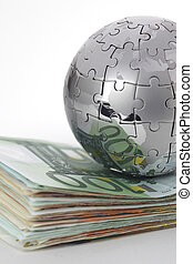 Metal puzzle globe with money on white background