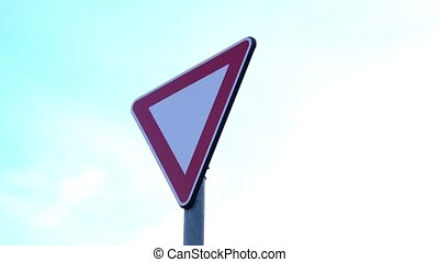 Metal road sign in triangle shape Yield instructing drivers give way against blue sky with white clouds close low angle shot