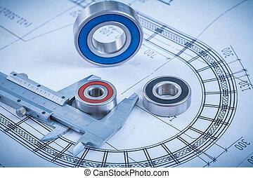 Metal roller bearings and trammel caliper on blueprint construct