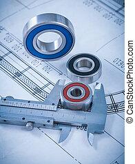Metal rolling bearings and slide caliper on blueprint constructi