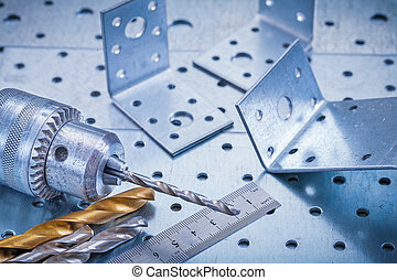 Metal ruler drill boring bits and angle bars on perforated...
