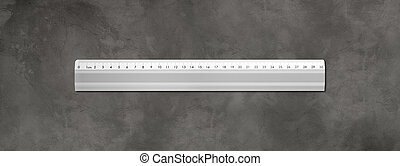 Metal ruler isolated on dark concrete background