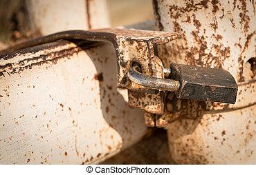 Metal rusty padlock on a closed gate