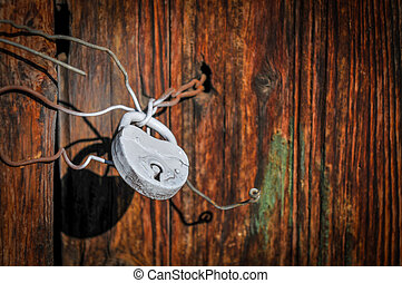 Metal rusty padlock on a closed old wooden door - Close-up...