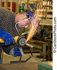 Metal Shop - Grinder - Student welder in metal shop, using a...