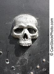 Metal skull door, fishing district of Genoa, Italy