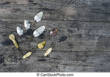 Metal spinners in the shape of a spoon of different colors for catching a predator on a vintage wooden background.