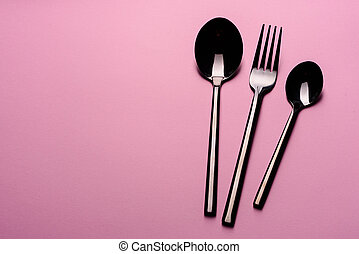 Metal Spoon and fork Isolated on pink background. Set of tableware ready for the meal