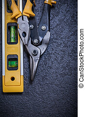 Metal steel cutter gripping tongs construction level on black background.