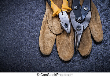 Metal steel cutter gripping tongs safety glove on black background.