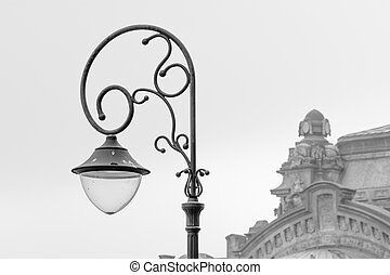 Metal street lamp with building behind. Black and white view of public metal street lamp and old building behind in winter time.